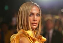 Jennifer con un hermoso traje amarilla y mira a la cámara